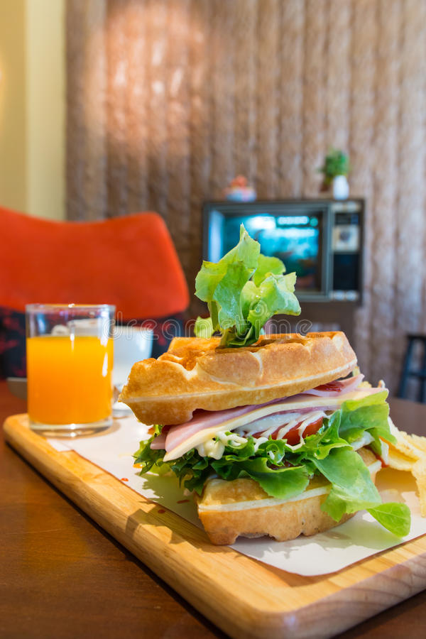 Waffle club sandwich with ham, cheese, egg, tomatoes, vegetable. And juice, delicious breakfast for a fresh morning stock images