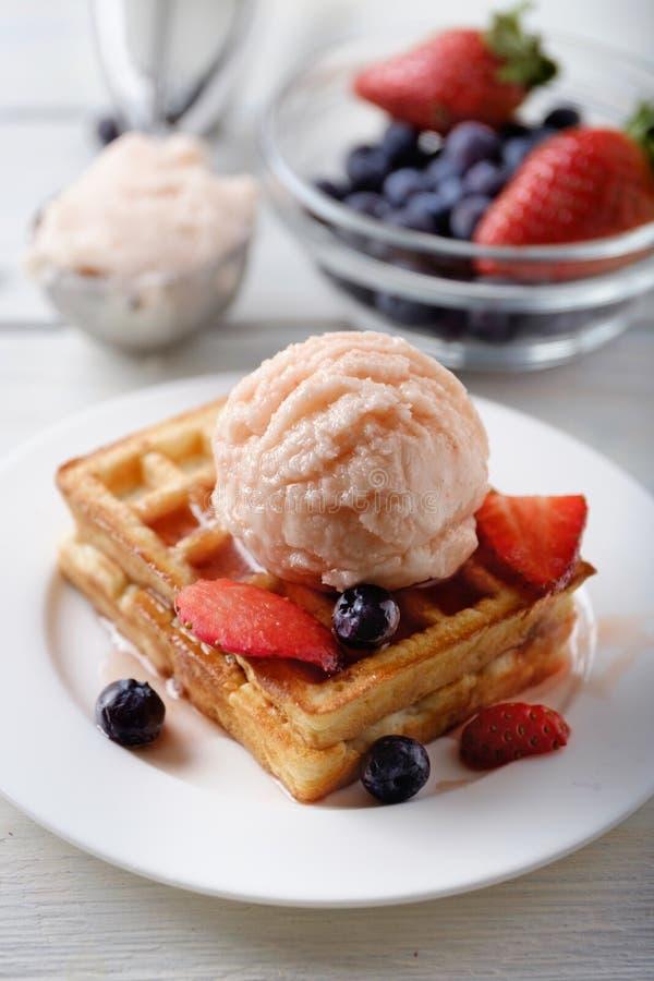 Waffle con il mestolo del gelato della fragola, del mirtillo, della fragola e della salsa immagine stock