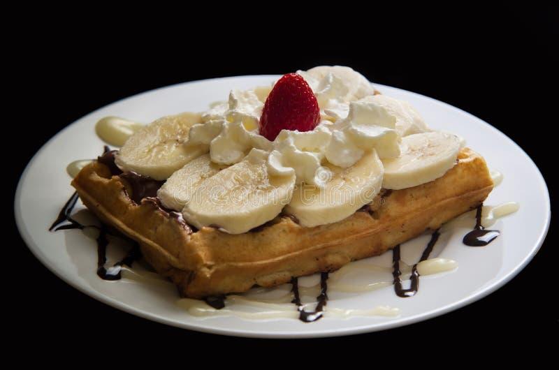 Waffle con la banana, il nutella, la panna montata e la fragola fotografia stock libera da diritti