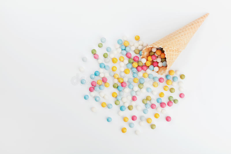 Waffle cone and heap colorful candy on white background from above. Flat lay style. stock image