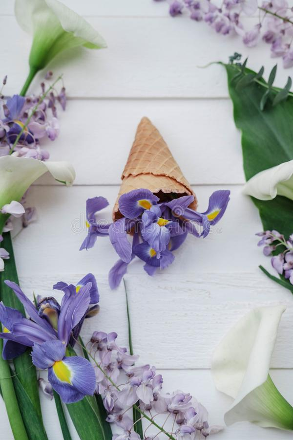 Waffle cone with wisteria, irises, callas flower on pink background. Flat lay, top view floral background. Waffle cone with wisteria, irises, callas flower on royalty free stock images