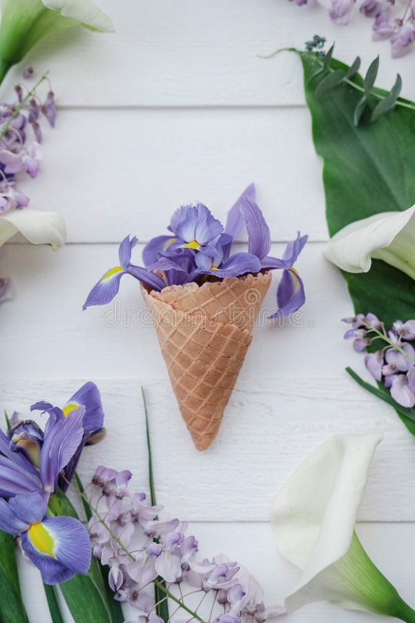 Waffle cone with wisteria, irises, callas flower on pink background. Flat lay, top view floral background. stock image