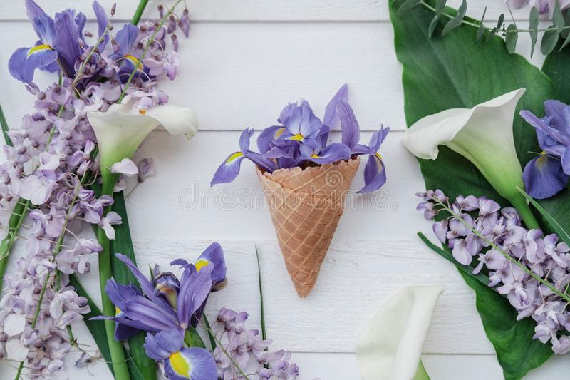 Waffle cone with wisteria, irises, callas flower on pink background. Flat lay, top view floral background. royalty free stock photos