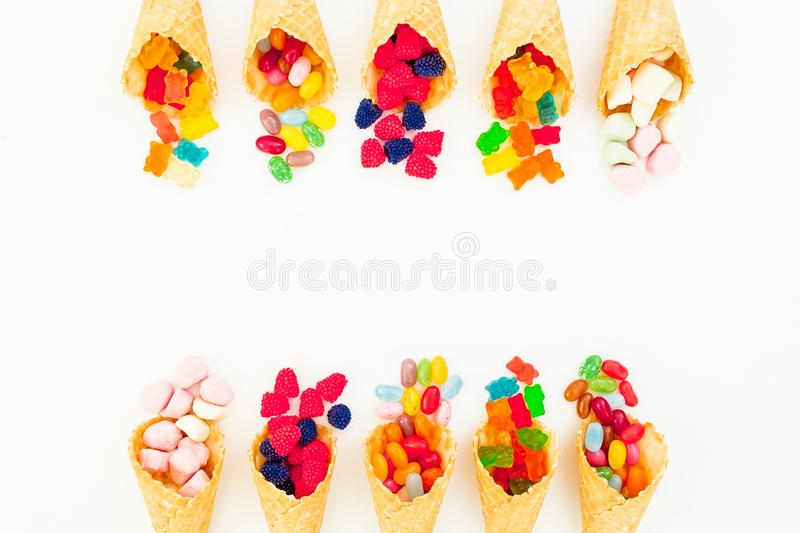 Waffle cones with assorted bright candy on white background. Flat lay, top view stock image