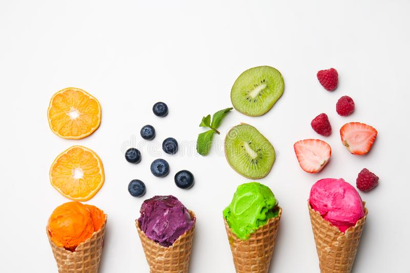 Waffle cones with delicious color ice cream, fruits and berries on white background stock photos