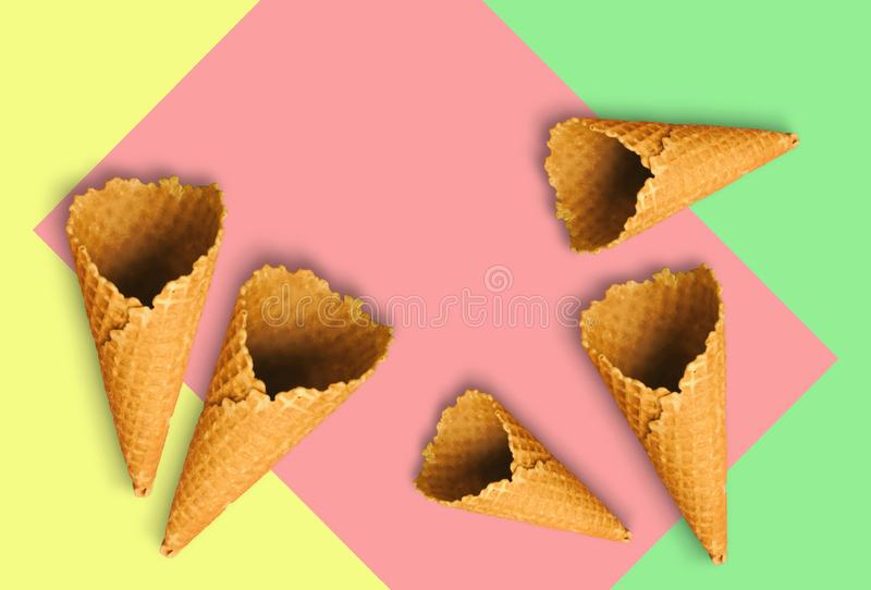 Waffle cones for ice cream on a light yellow, sweet pink and light green background with copy space for insertion or decoration of royalty free stock photo