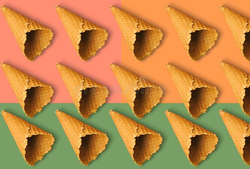 Waffle cones for ice cream on an orange, green and pink background with copy space for insertion or decoration of text, logo or royalty free stock image