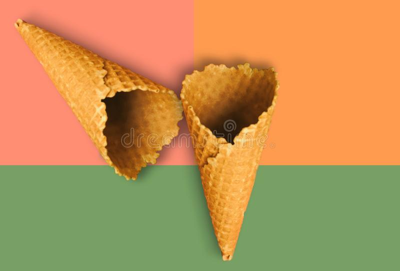 Waffle cones for ice cream on an orange, pink and green background with copy space for insertion or decoration of text, logo or royalty free stock image