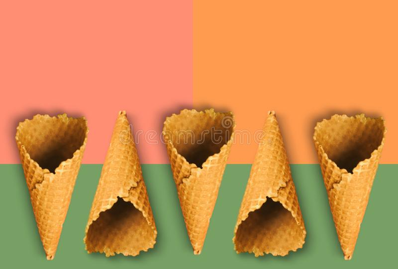 Waffle cones for ice cream on an orange, pink and green background with copy space for insertion or decoration of text, logo or stock photography