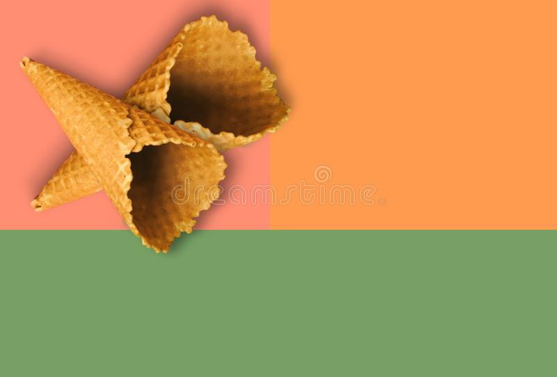 Waffle cones for ice cream on an orange, pink and green background with copy space for insertion or decoration of text, logo or royalty free stock images
