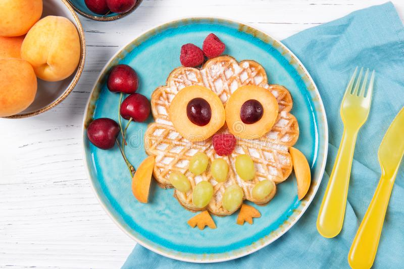 Waffle with fruits and berries in the shape of cute owl with balloons, food for kids idea, top view royalty free stock photography