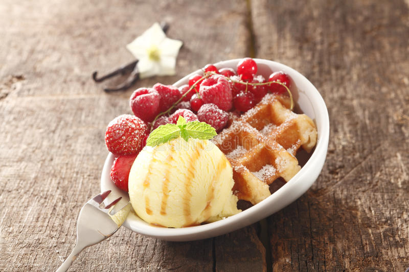 Waffle, icecream and berry dessert. A bowl on a wooden table filled with a golden waffle, icecream and assortment of red berries sprinkled with sugar royalty free stock images