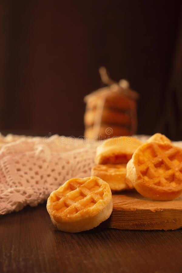 Waffle round-shaped biscuits on the table, white plate stock images