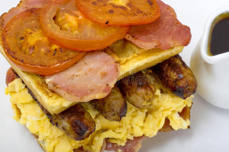 Waffle Stack Breakfast with Maple Syrup. Breakfast plate of Double Waffle stack with scrambled eggs, bacon medallions, sausage tomatoes and a jug of maple syrup stock photos