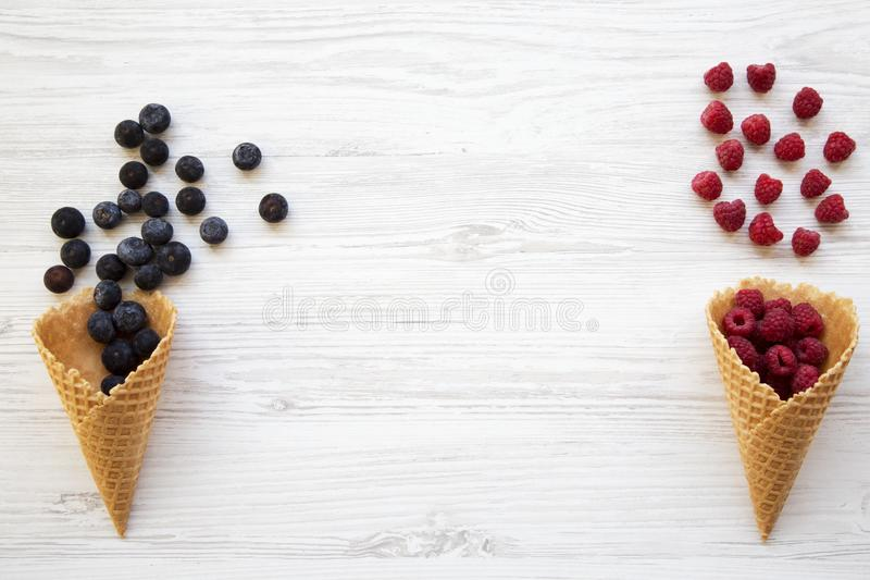 Waffle sweet ice cream cones with raspberries and blueberries over white wooden background, top view. Flat lay. royalty free stock photo