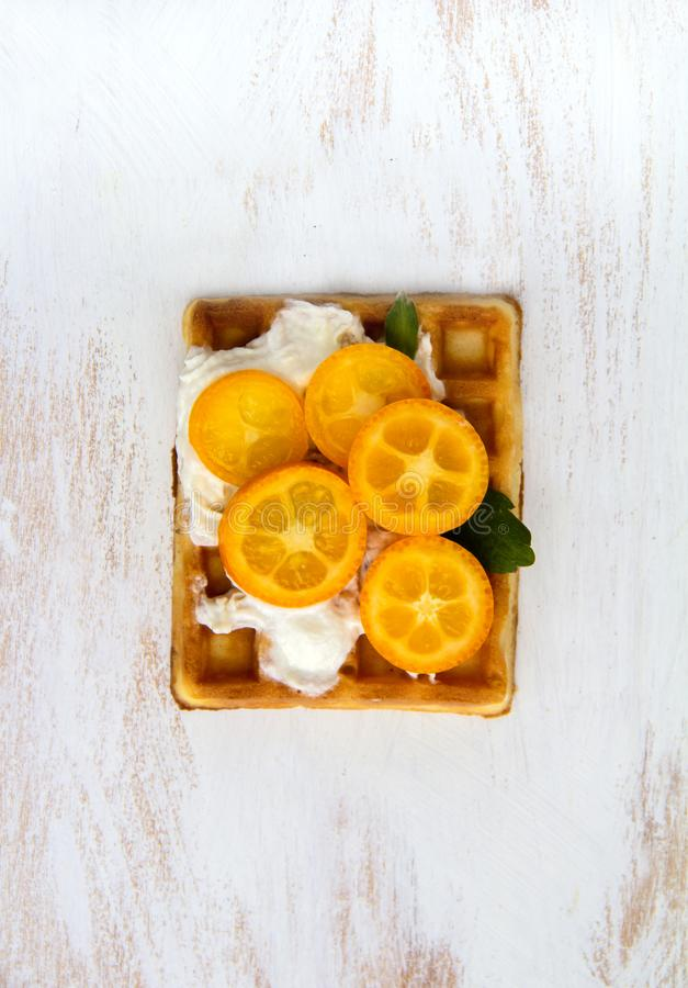 Waffle vienense com o Kumquat do fruto e do creme foto de stock