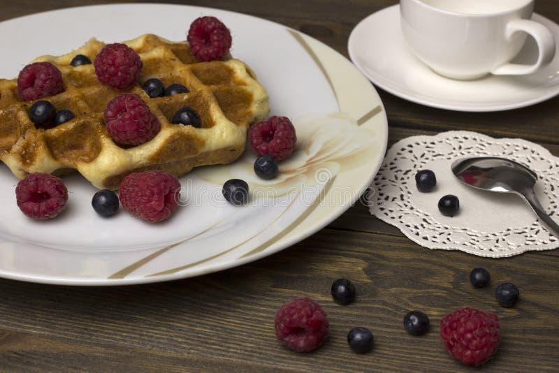 Waffles в белой плите с ягодами на таблице стоковое фото
