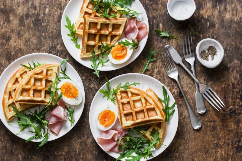 Waffles картошки смачные с вареным яйцом, ветчиной и arugula на деревянной предпосылке, взгляд сверху Служат завтрак, закуска, за стоковая фотография rf
