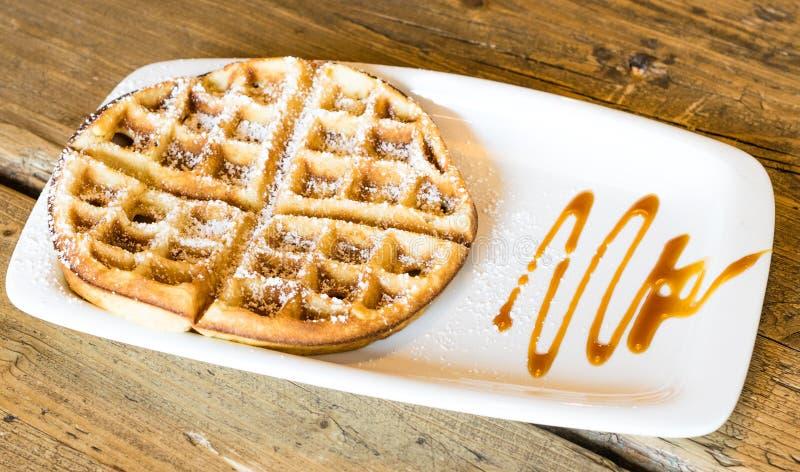 Waffles с соусом карамельки на деревянной предпосылке стоковые изображения