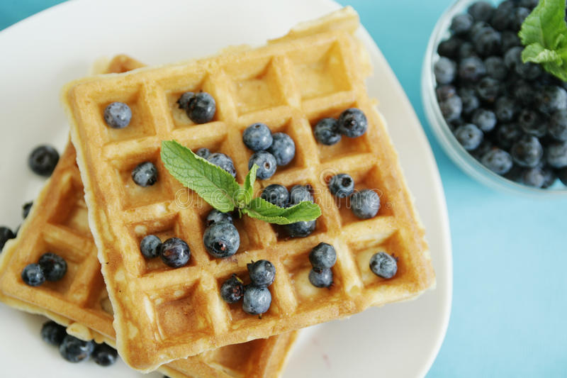 Waffles. Blueberries on waffles on a blue background royalty free stock images