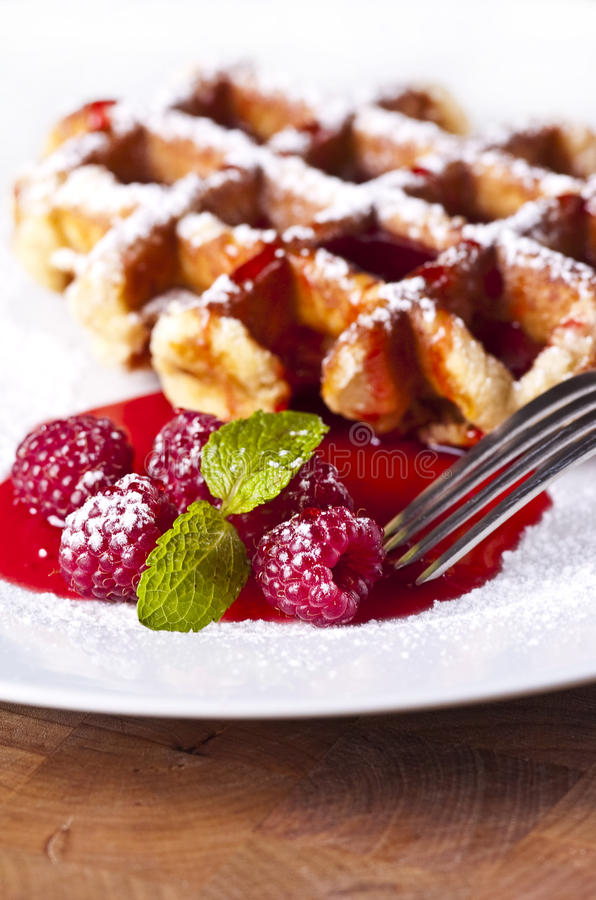 Waffles. Delicious Belgian waffles garnished with fresh raspberries stock photos