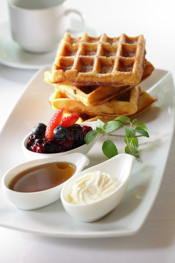 Waffles. A plate of waffles with fresh fruits, honey and cream stock photos