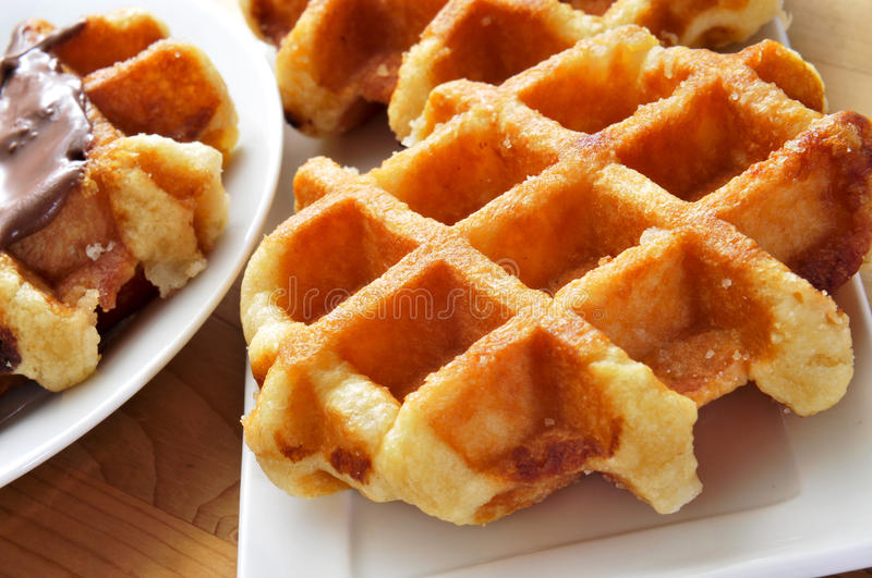 Waffles. Some plates with waffles on a wooden table royalty free stock photography