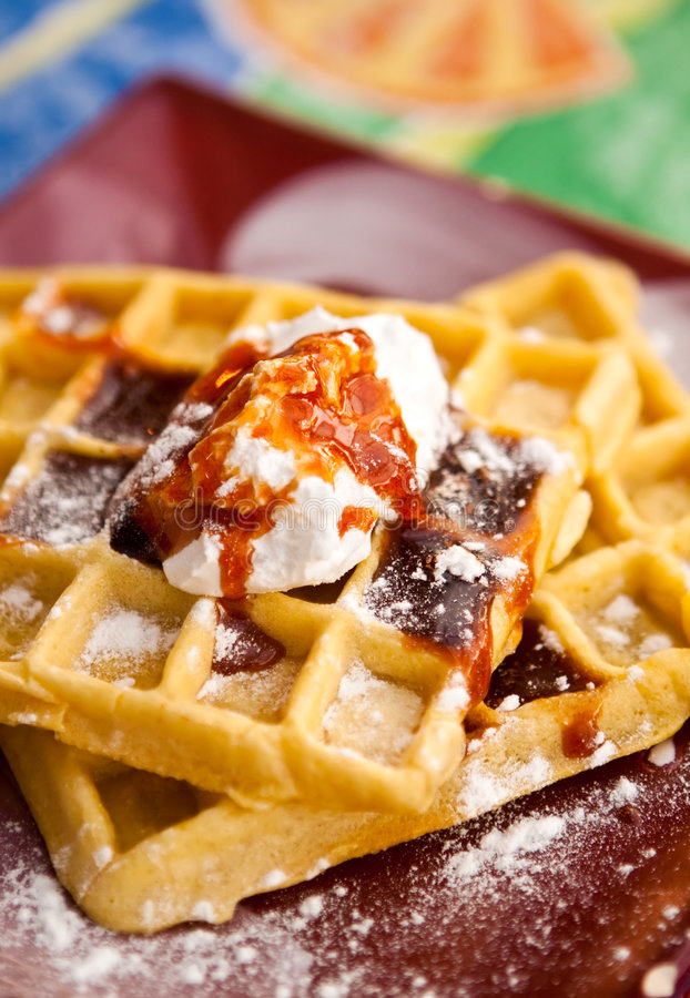 Waffles. Golden waffles topped with whipped butter (or whipped cream), dark maple syrup, and dusted with powdered sugar stock photos