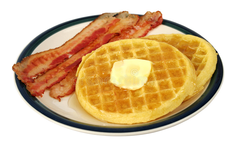 Waffles & Bacon Isolated. A plate of waffles with butter and syrup with bacon on the side. Complete plate, isolated royalty free stock images