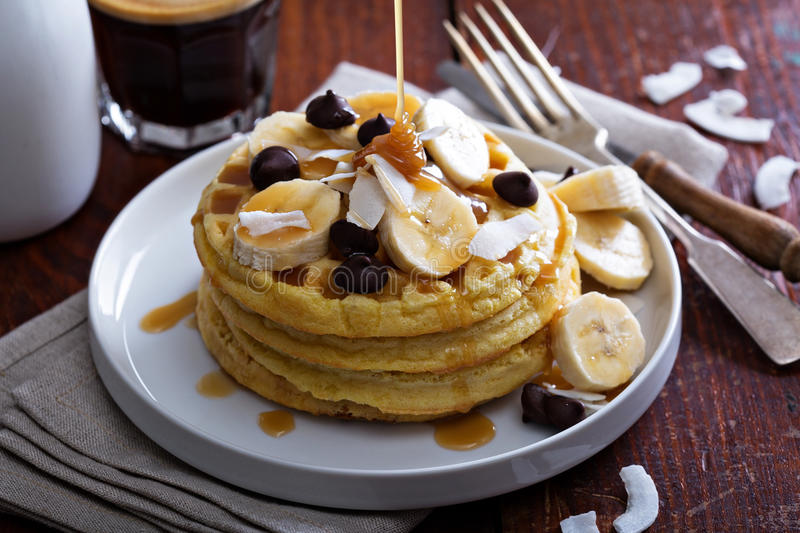 Waffles with banana slices and chocolate. Waffles with banana slices, caramel and chocolate stock photo