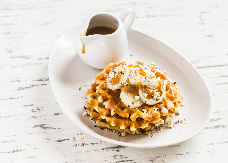 Waffles with banana slices, nuts and caramel sauce royalty free stock images