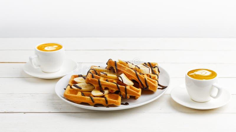Waffles belgas caseiros com as fatias da banana cobertas com chocolate e duas x?caras de caf? na tabela de madeira branca imagens de stock