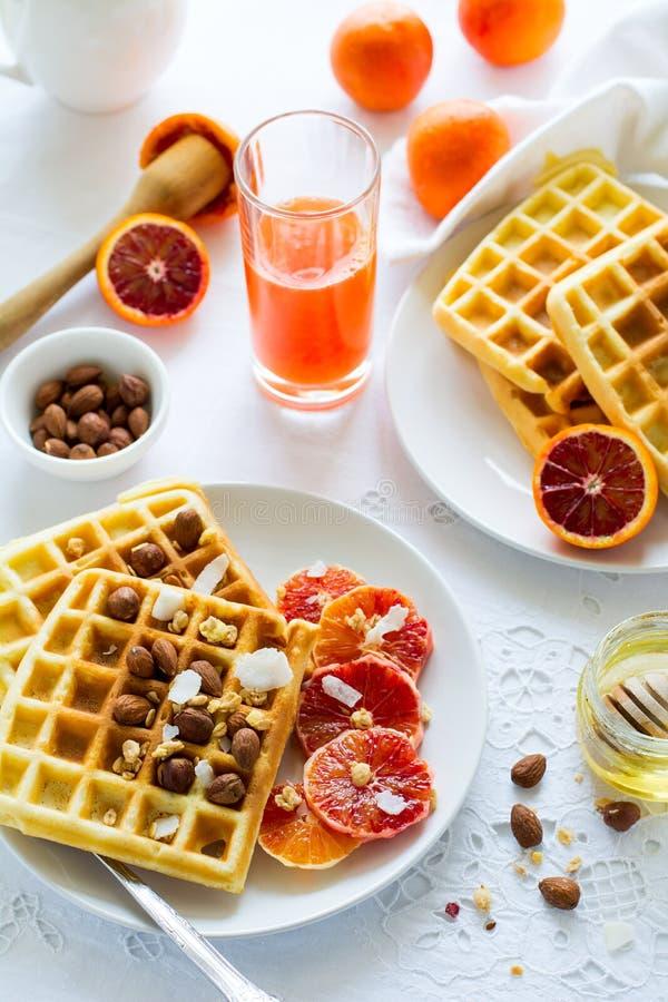 Waffles belgas do café da manhã saudável com porcas e laranjas pigmentadas fotografia de stock