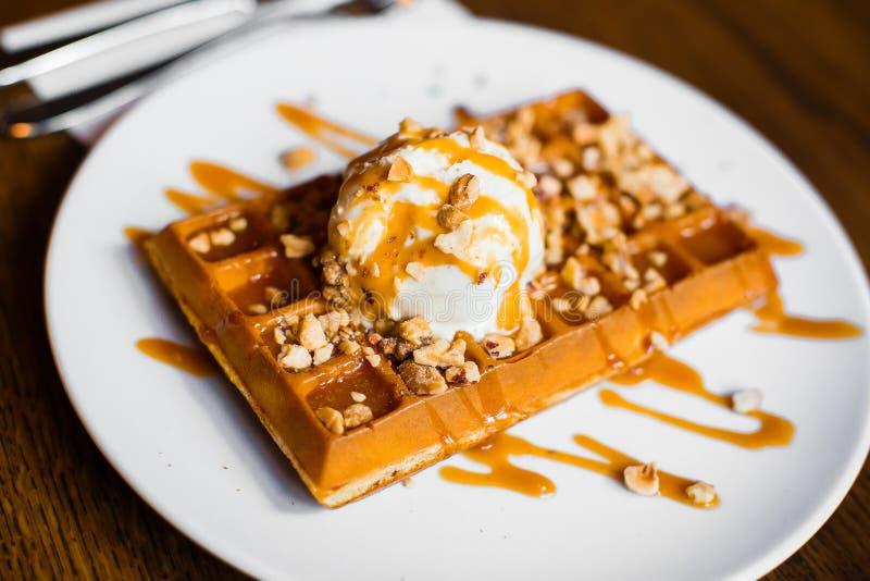 Waffles belgas doces deliciosos com gelado branco saboroso com caramelo e porcas Opinião lateral do close-up foto de stock