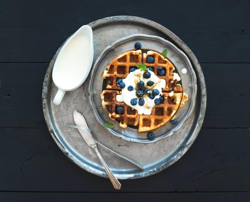 Waffles belgas macios com mirtilos, mel e chantiliy na placa de metal do vintage sobre o fundo de madeira preto, parte superior imagem de stock royalty free