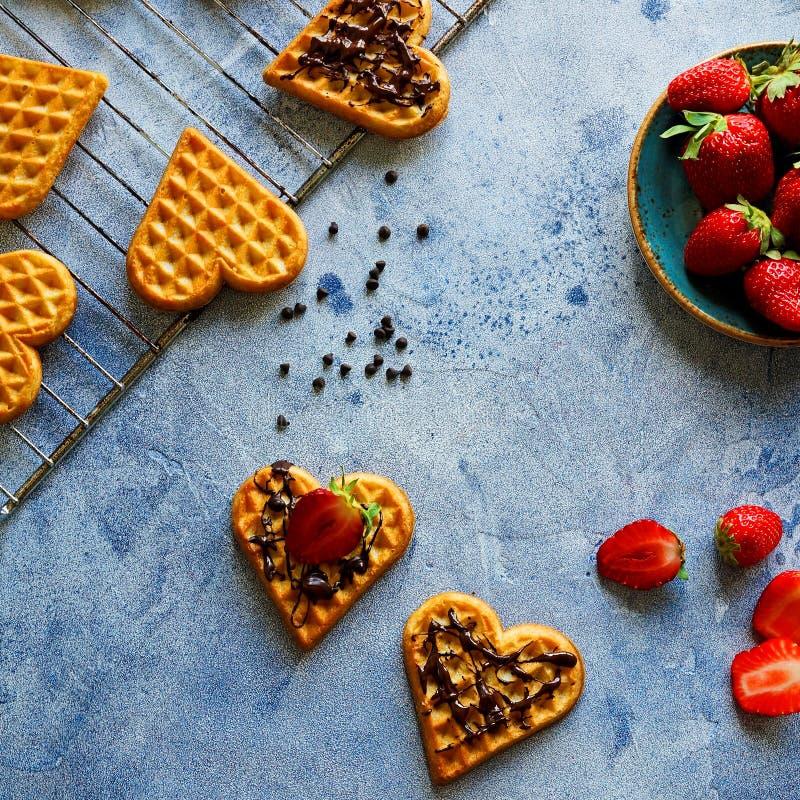 Waffles belgas na forma dos corações com morangos e cobertura frescas do chocolate na tabela azul imagens de stock royalty free