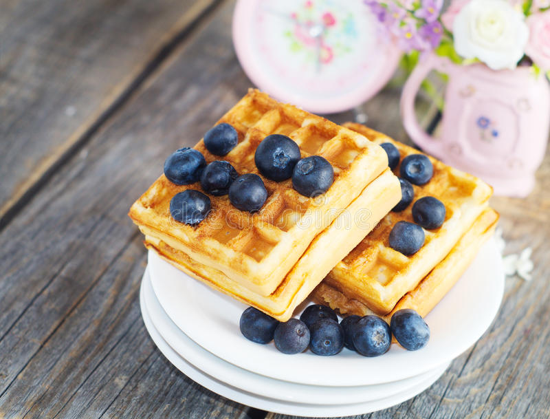 Waffles. Belgian waffles with blueberries on the wooden rustic surface stock photography