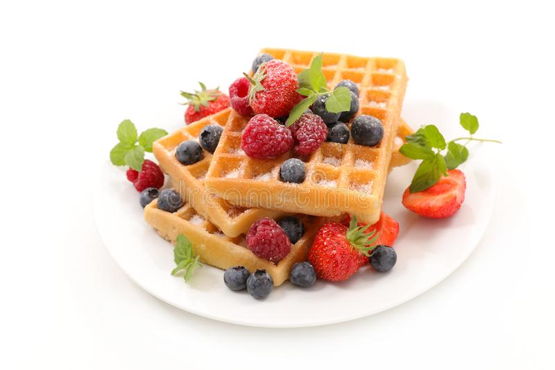Waffles with berries fruits. On white background royalty free stock photos