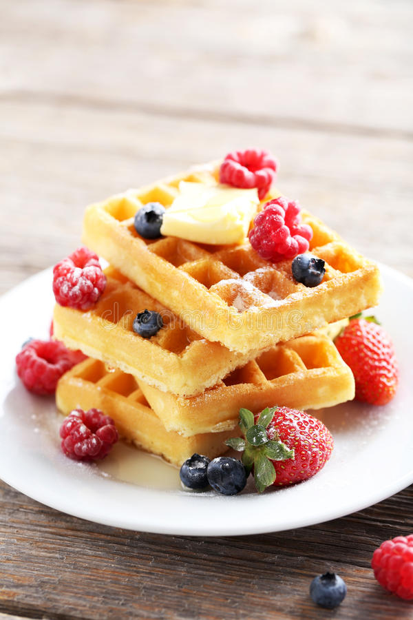 Waffles with berries. Homemade waffles with berries in plate on grey wooden table stock photography