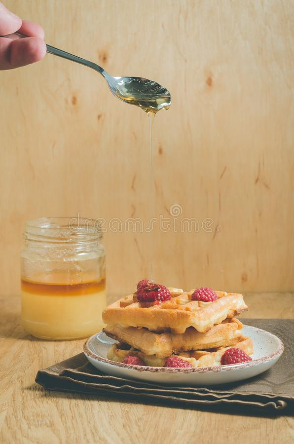 Waffles with berries, honey in plate/waffles with berries, honey in plate on a old wooden background, selective focus. Breakfast, dessert, yummy, raspberry royalty free stock images