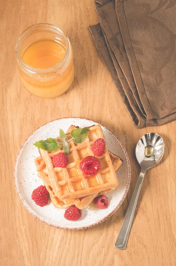 Waffles with berries, honey in plate/waffles with berries, honey in plate on a old wooden background, top view. Breakfast, dessert, yummy, raspberry royalty free stock photography