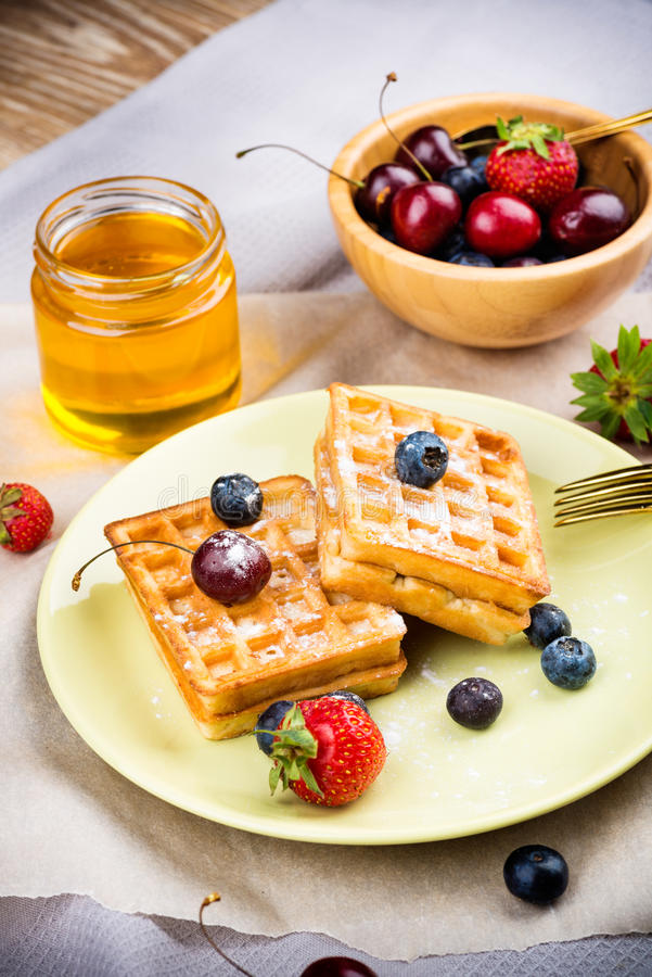 Waffles with berries. On wooden background stock photos