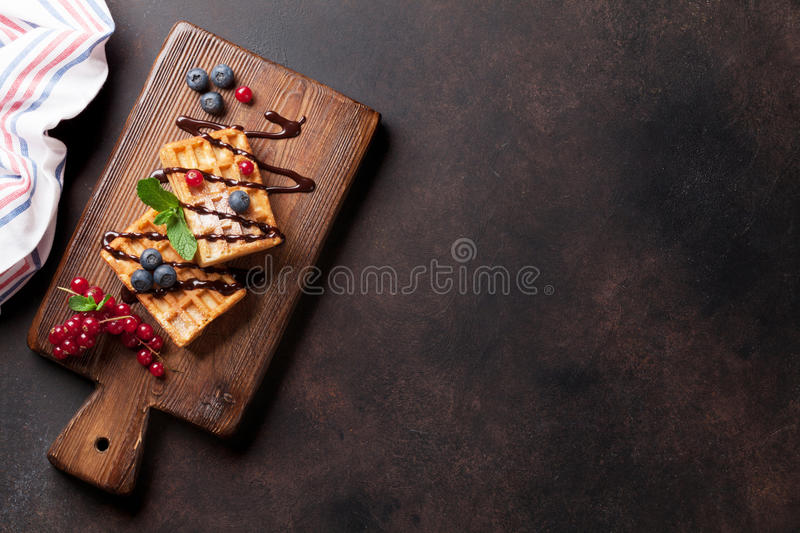 Waffles and berries. On wooden board. Top view with copy space stock photos