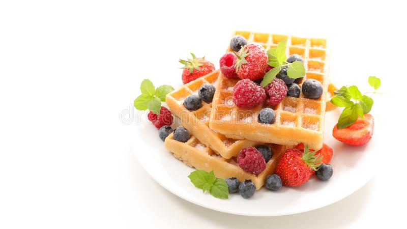 Waffles and berry fruit. On white stock photography