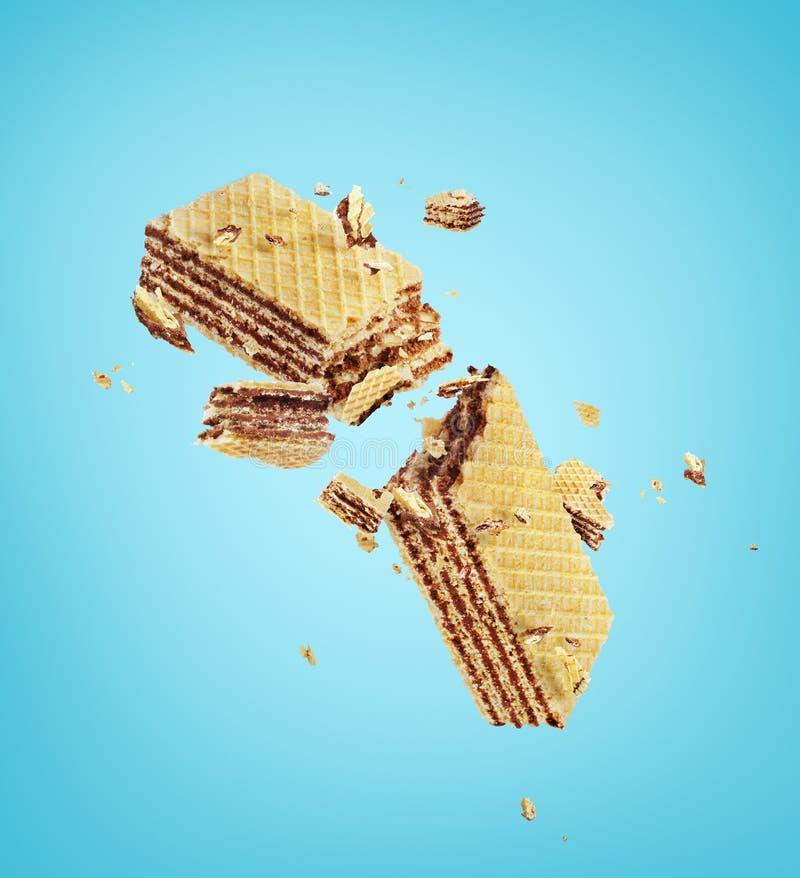 Waffles broken in half. On blue royalty free stock image