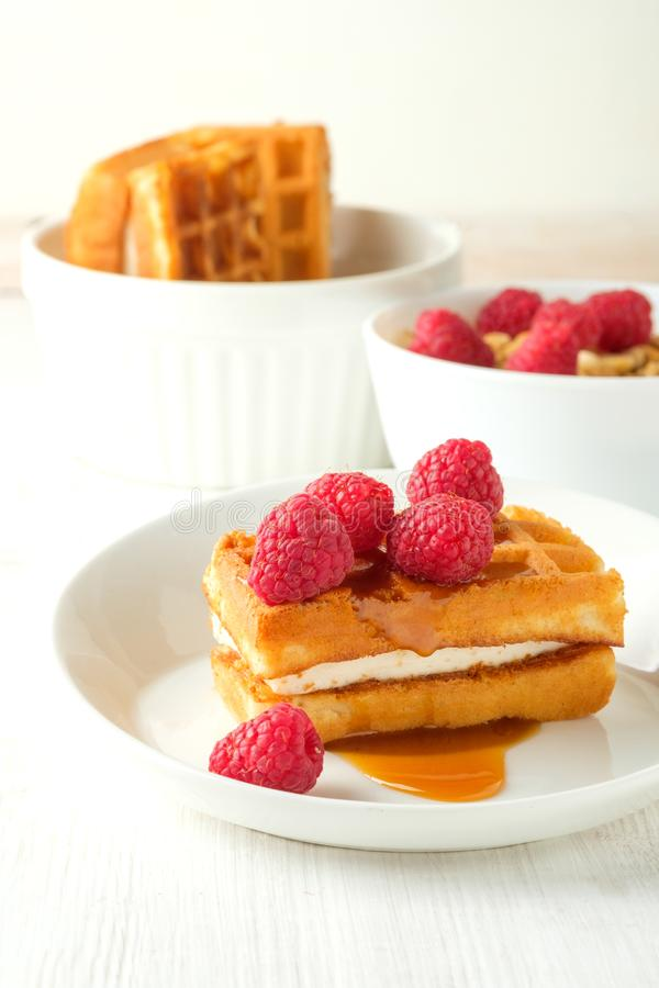 Waffles with caramel syrup and raspberries isolated on white background, top view stock photo