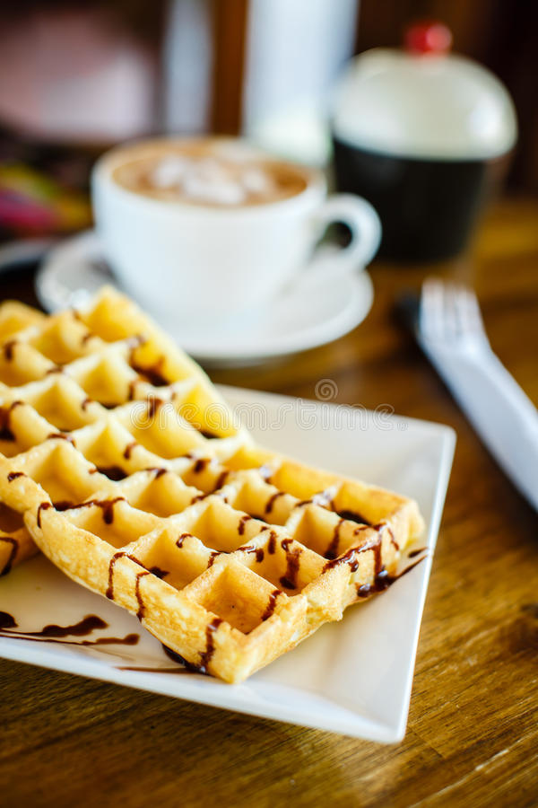 Waffles with chocolate and coffee on the wooden table stock photography