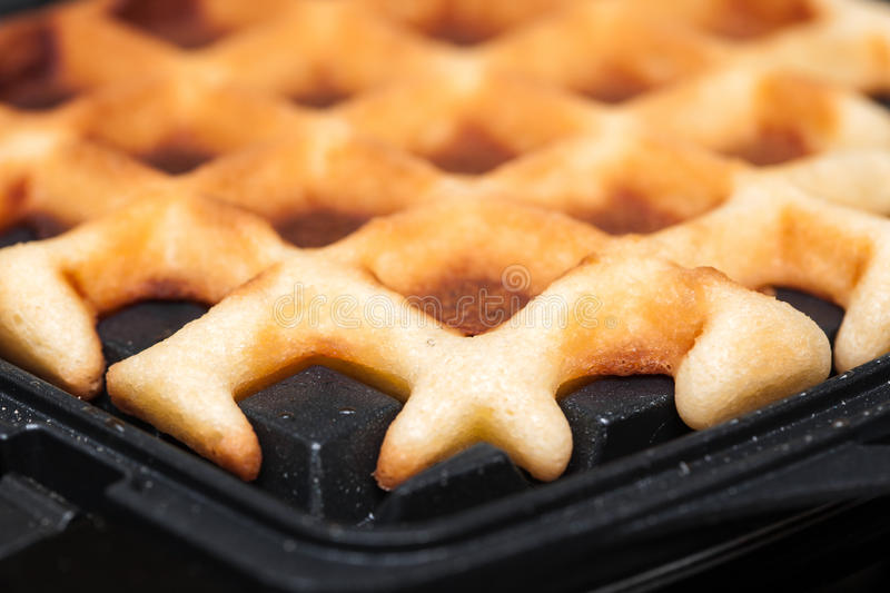 Waffles are cooked in waffle iron. Homemade waffles are cooked in the waffle iron. close up royalty free stock image