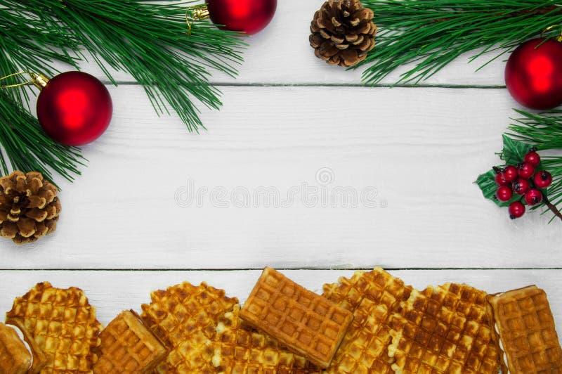 Waffles e árvore de Natal do ramo e bola vermelha com o cone no fundo de madeira branco do vintage foto de stock