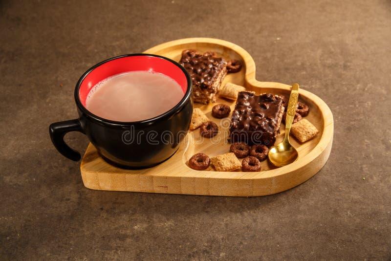 Waffles e cookies do chocolate em uma bandeja de madeira na forma de um coração e de um copo do chocolate quente foto de stock royalty free